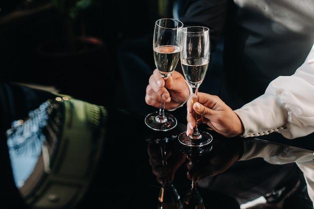 Mężczyzna i kobieta trzymają w rękach kieliszki do szampana z bliska.
