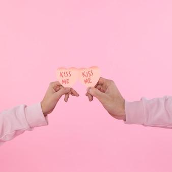 Mężczyzna i kobieta trzymając papier ozdobny symbole serca