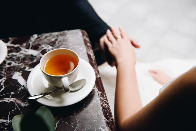 Mężczyzna i kobieta, trzymając ręce siedząc w kawiarni lub restauracji, skupić się na filiżance herbaty z przodu