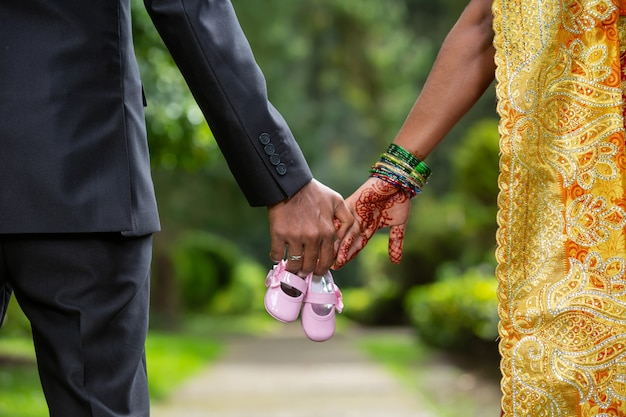 Mężczyzna i kobieta, trzymając się za ręce i buty dla niemowląt