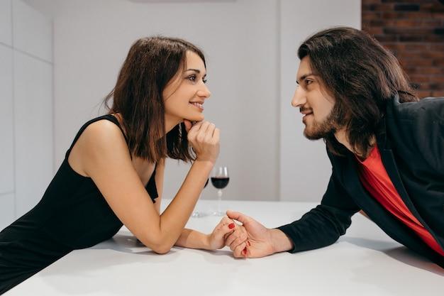 Mężczyzna i kobieta, trzymając się za ręce w romantycznej scenerii domu