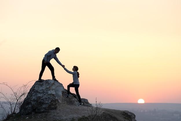 Mężczyzna i kobieta turystów pomagających sobie nawzajem wspinać się po kamieniu o zachodzie słońca w górach