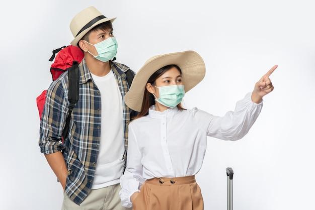 Mężczyzna i kobieta ubrani do podróży, noszący maski wraz z bagażem