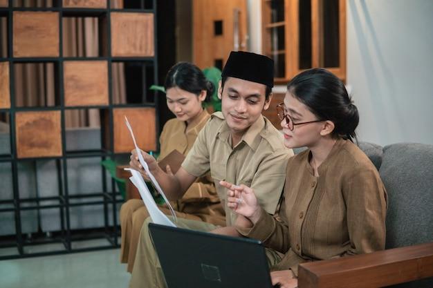 Mężczyzna i kobieta urzędnicy państwowi trzymający i patrzący na dokumenty, siedząc podczas pracy online w domu