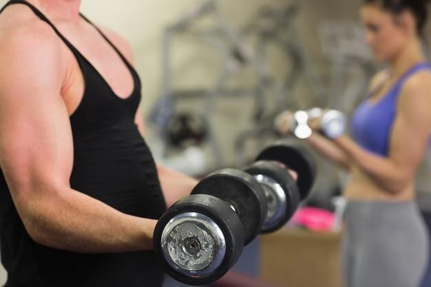 Mężczyzna i kobieta używa dumbbells w gym