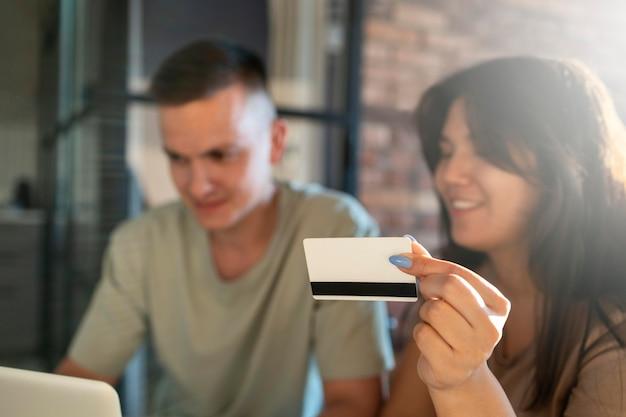 Mężczyzna i kobieta używają laptopa do zakupów online za pomocą karty kredytowej