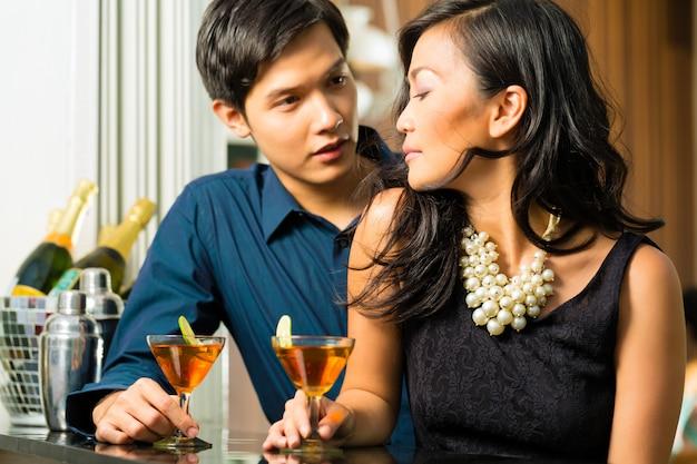 Mężczyzna i kobieta w azji w barze z koktajlami