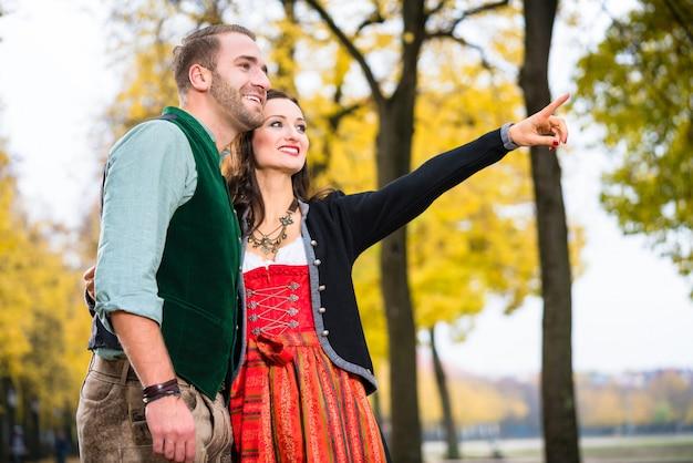 Mężczyzna i kobieta w bawarskim tracht, dziewczyny wskazywać