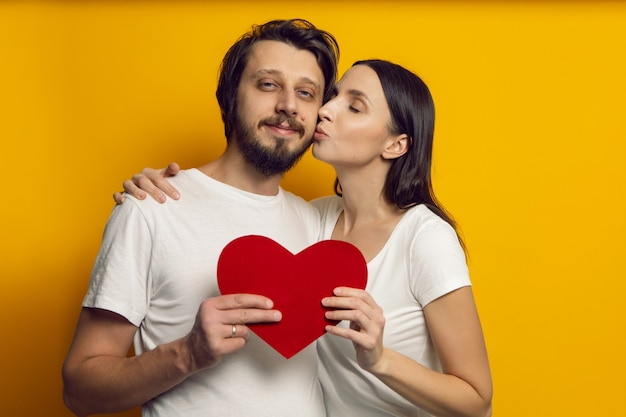 Mężczyzna i kobieta w białych koszulkach trzymają papierowe serce w walentynki