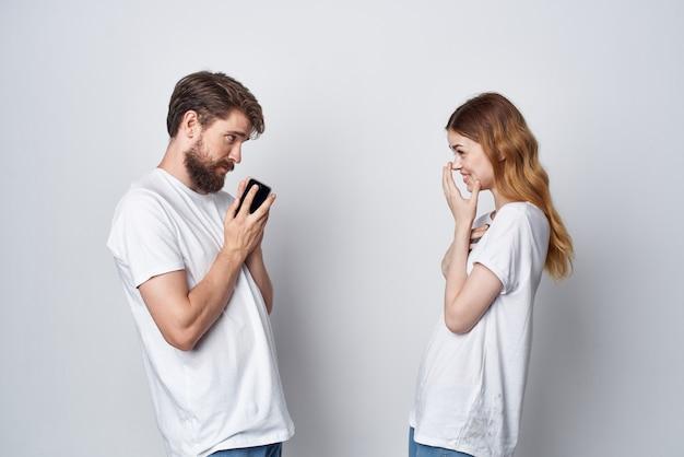 Mężczyzna i kobieta w białych koszulkach z telefonami w rękach jasnym tle