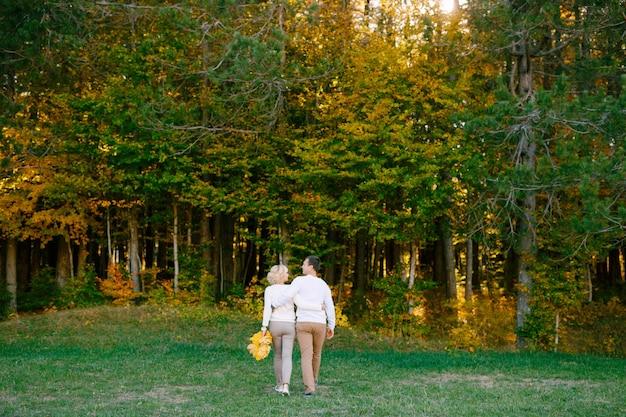 Mężczyzna i kobieta w białych swetrach i beżowych spodniach przytulają się do lasu