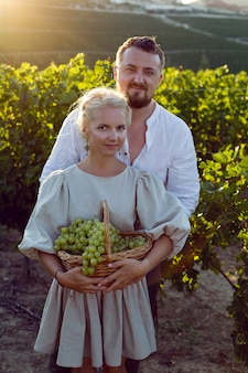 Mężczyzna i kobieta w białych ubraniach stoją w polu winogron o zachodzie słońca trzymając kosz winogron