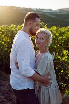 Mężczyzna i kobieta w białych ubraniach stoją w polu winogron o zachodzie słońca
