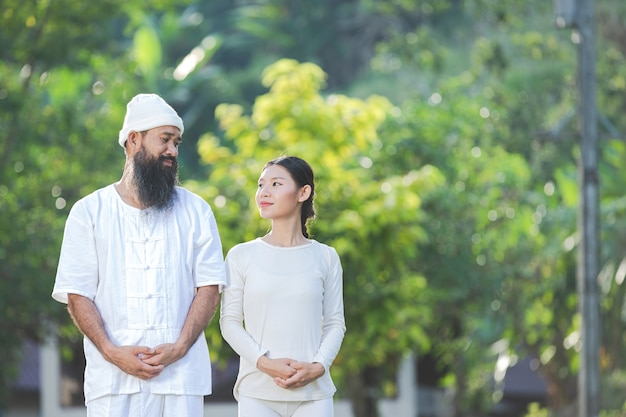 Mężczyzna i kobieta w białym stroju uśmiechają się do siebie w emocjach szczęścia