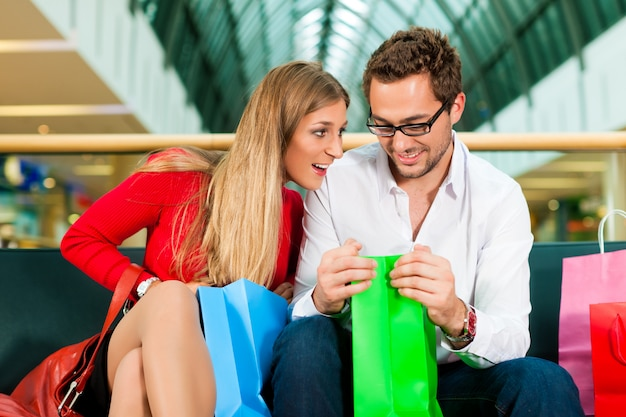 Mężczyzna i kobieta w centrum handlowym z torbami
