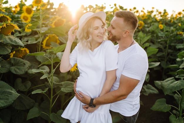 Mężczyzna i kobieta w ciąży przytulają się czule stojąc na polu z wysokimi słonecznikami wokół nich