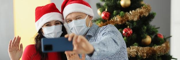 Mężczyzna i kobieta w czapkach świętego mikołaja i maskach ochronnych na twarzach trzymają telefon komórkowy i machają w pobliżu
