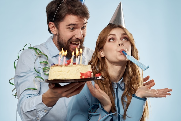Mężczyzna i kobieta w czapkach z tortem urodzinowym na niebieskim tle