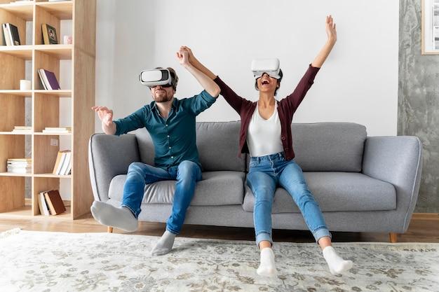 Mężczyzna i kobieta w domu na kanapie z zestawem słuchawkowym wirtualnej rzeczywistości