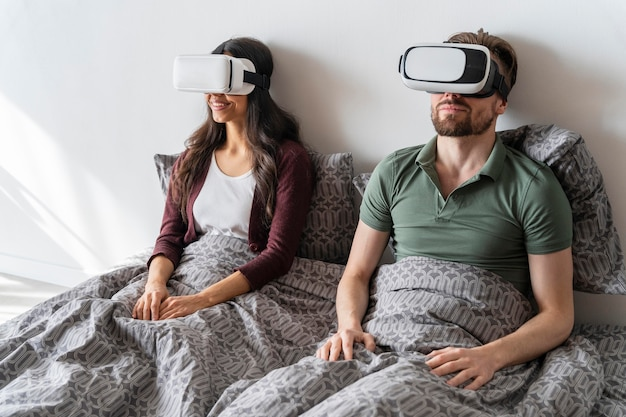 Mężczyzna i kobieta w domu przy użyciu zestawu słuchawkowego wirtualnej rzeczywistości
