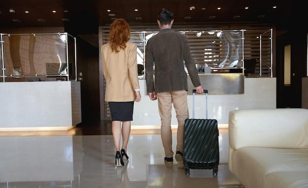Mężczyzna i kobieta w eleganckich ubraniach idących w kierunku recepcji na odprawę