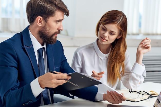 Mężczyzna i kobieta w garniturach patrząc na biuro technologii tabletu