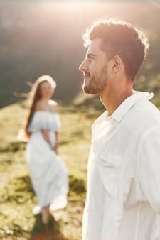 Mężczyzna i kobieta w górach. młoda para zakochana o zachodzie słońca. kobieta w niebieskiej sukience.