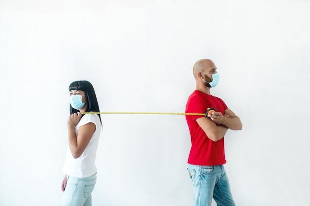 Mężczyzna i kobieta w maskach stoją plecami do siebie i trzymają między sobą taśmę mierniczą, demonstrując dystans społeczny