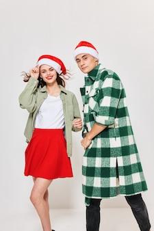 Mężczyzna i kobieta w modnych ciuchach i świątecznym kapeluszu na jasnym tle.