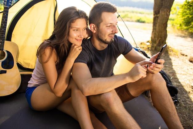 Mężczyzna i kobieta w pobliżu namiotu z tabletem.