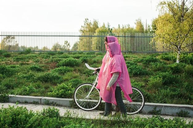 Mężczyzna i kobieta w różowych plastikowych płaszczach przeciwdeszczowych idących drogą z rowerem na randkę