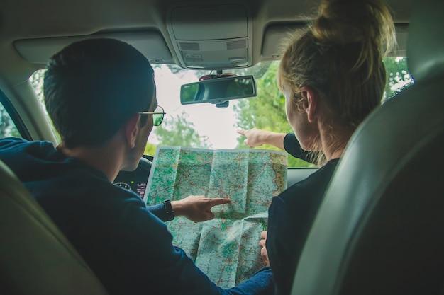Mężczyzna i kobieta w samochodzie patrzą na mapę