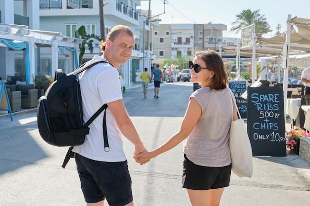 Mężczyzna i kobieta w średnim wieku idą razem trzymając się za ręce