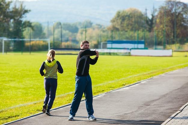 Mężczyzna i kobieta w strojach sportowych uprawiają sport na stadionie