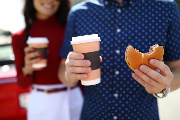 Mężczyzna i kobieta w tle trzymają kawę i hamburgera