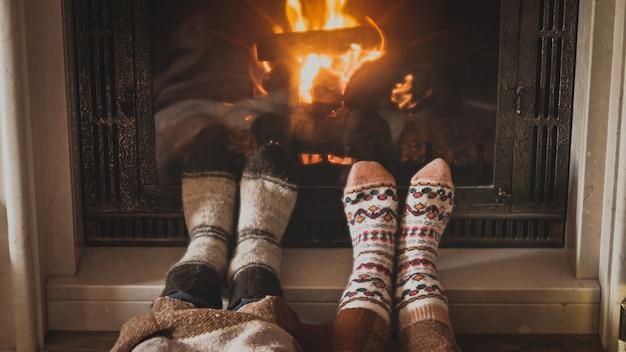 Mężczyzna i kobieta w wełnianych skarpetkach ogrzewają stopy przy płonącym kominku