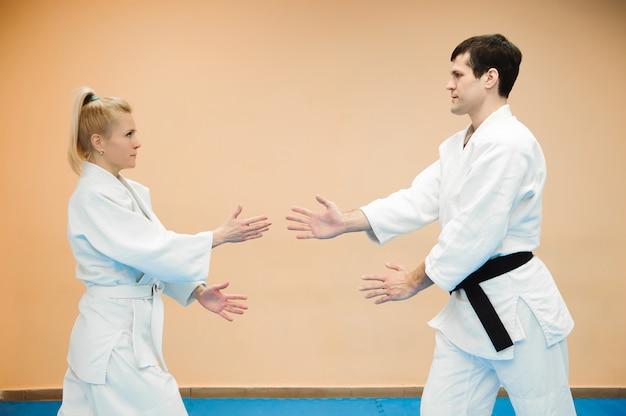 Mężczyzna i kobieta walczą na treningu aikido w szkole sztuk walki