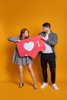 Mężczyzna i kobieta walczą o uwagę, trzymając jak znak, nie mogą się dzielić, kłócą się, na pomarańczowej ścianie