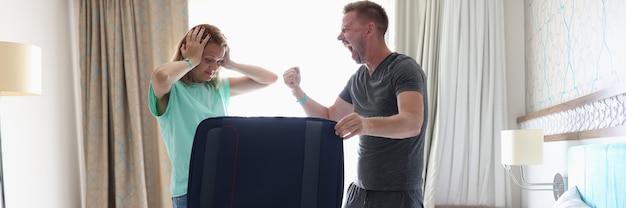 Mężczyzna i kobieta walczą w sypialni obok walizki
