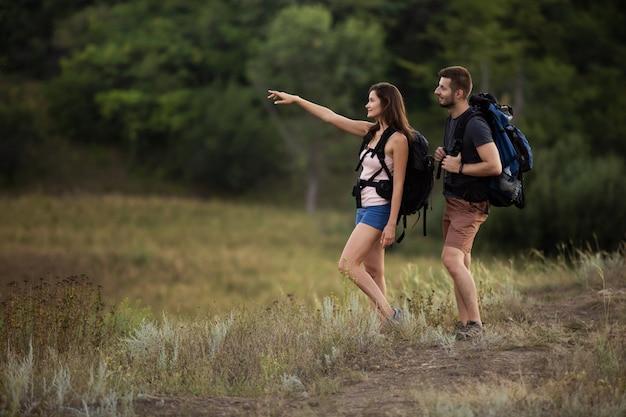 Mężczyzna i kobieta wędrują po górach z plecakami. dziewczyna wskazuje właściwą drogę
