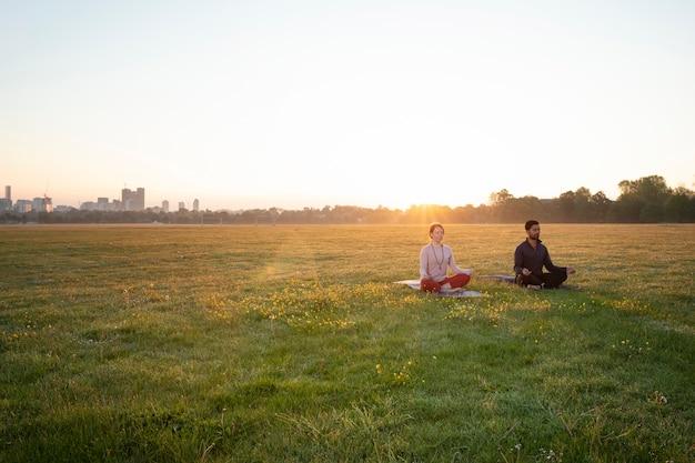 Mężczyzna i kobieta wspólnie uprawiają jogę na świeżym powietrzu