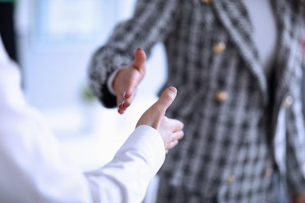 Mężczyzna i kobieta wyciągają ręce do uścisku dłoni