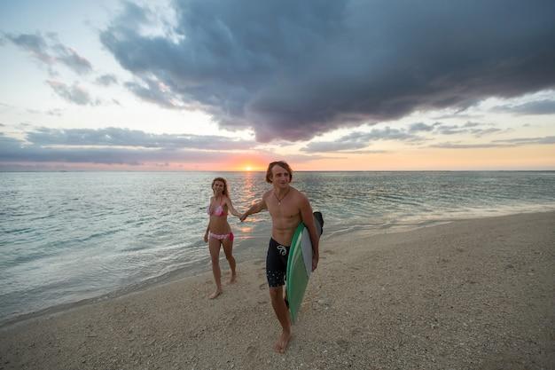 Mężczyzna i kobieta z deskami surfingowymi o zachodzie słońca