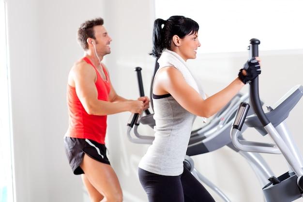 Mężczyzna i kobieta z eliptyczny orbitrek w siłowni
