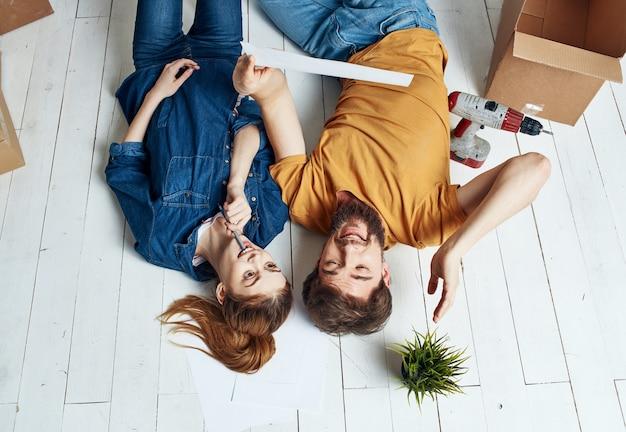 Mężczyzna i kobieta z pudełkami na podłodze kwiat w doniczce w ruchu do naprawy.