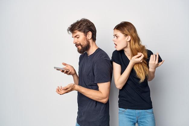 Mężczyzna i kobieta z telefonem w ręku emocje jasne tło