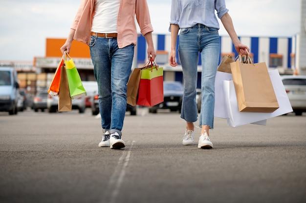 Mężczyzna i kobieta z torbami na parkingu w supermarkecie