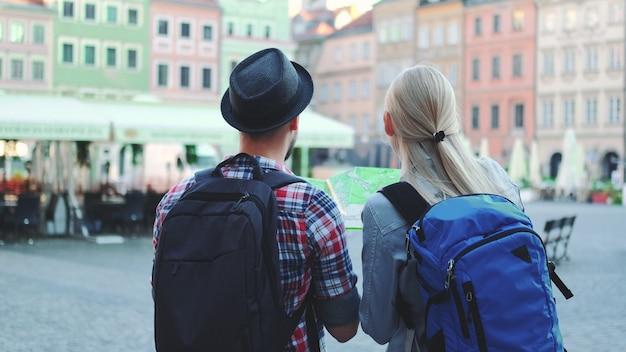 Mężczyzna i kobieta z torby sprawdzanie mapy na centralnym placu miasta