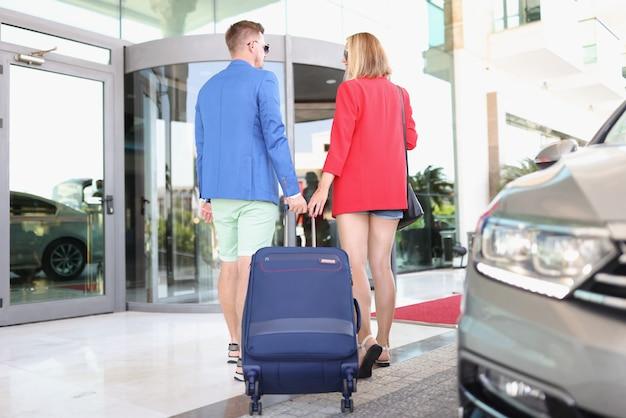 Mężczyzna i kobieta z walizką wysiadają z taksówki do budynku lotniska