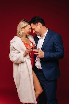 Mężczyzna i kobieta zakochani przy lampce szampana na czerwonym tle uścisku.